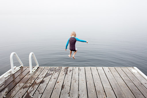little boy jumping into misty lake from cottage dock