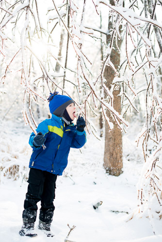 Little boy outdoors licking icicle in ice and snow in winter in fur hat lifestyle portrait jp danko toronto commercial photographer