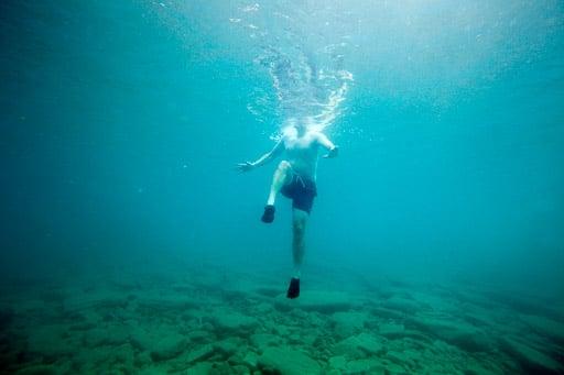 Man treading water in blue lake
