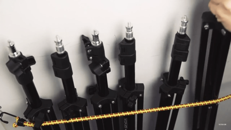A simple DIY method for storing stands and tripods: use two bungee cords